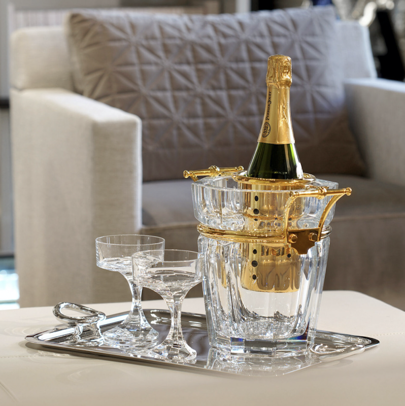 HARCOURT champagne cooler. A symbol of elegance, champagne adorns itself in the most beautiful setting possible. The Harcourt champagne bucket enhances the clear crystal's purity with silver or gold-plated handles, making it a luxurious table element. NARCISSE champagne coupes perfectly complete the scene. NARCISSE COUPE by BORIS TABACOFF IMAGINED the NARCISSE set back in 1971. In gift-set of two champagne coupes, the NARCISSE glasses add a sublime touch to the most original dinner table with its timeless design.